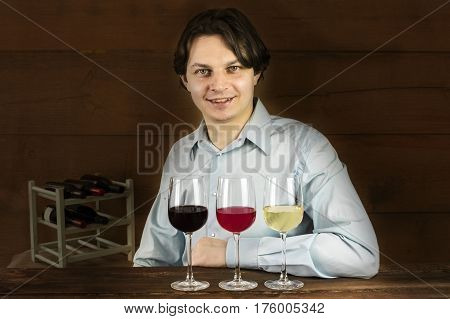 A photo of an enologist tasting wine at a winery, with three glasses in front of him
