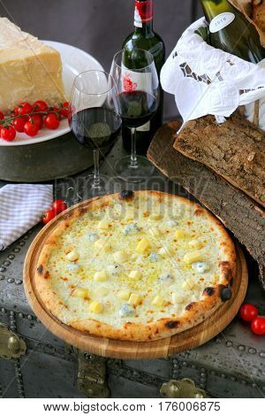 charming rustic still life with Dor Blue cheese pizza, cherry tomatoes and red wine