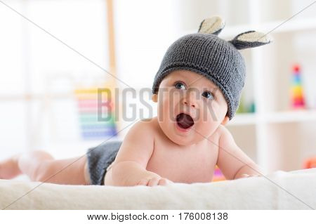 Smiling cute baby infant child in rabbit costume lying on bed in nursery