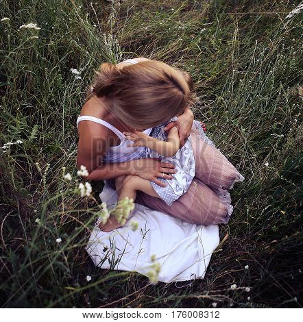 young woman withe her small daughter in the meadow. breastfeeding in the meadow. young woman