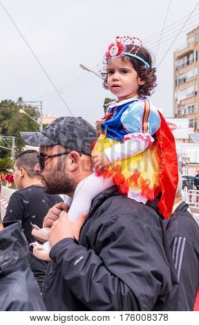 Nahariya Israel March 10 2017: Girl dressed like a princess sits on her father's shoulders and looks at the traditional annual parade