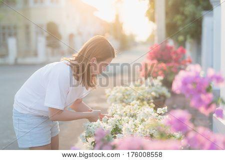 Asian woman pruning flowers and plants outdoor.
