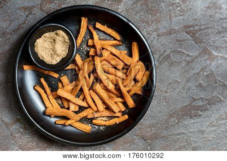 Sweet potato fries with spiced salt.  Black rustic dish, top view, over slate.
