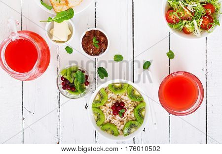 Tasty And Healthy Oatmeal Porridge With Kiwi And Cranberry. Salad And Juice. Healthy Breakfast. Fitn