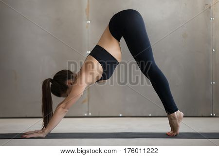 Young attractive woman practicing yoga, standing in Downward facing dog exercise, adho mukha svanasana pose, working out, wearing black sportswear, cool urban style, full length, grey studio