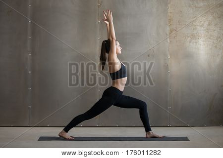 Young attractive woman practicing yoga, standing in Warrior one exercise, Virabhadrasana I pose, working out, wearing black sportswear, cool urban style, full length, grey studio background, side view