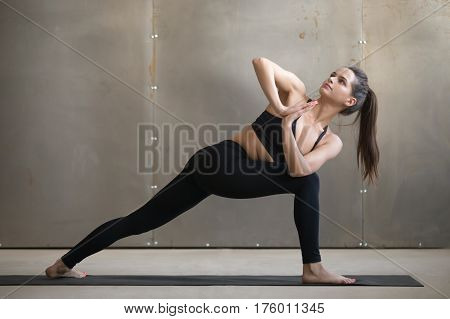 Young attractive yogi woman practicing yoga, standing in Parivrtta Parsvakonasana exercise, Revolved Side Angle pose, working out, wearing black sportswear, cool urban style, full length, grey studio