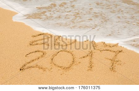 digits 2016 and 2017 on the beach sand - concept of new yearvacationtravel and passing of time