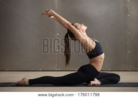 Young attractive woman practicing yoga, stretching in One Legged King Pigeon exercise, Eka Pada Raja Kapotasana pose, working out, wearing black sportswear, cool urban style, full length, grey studio