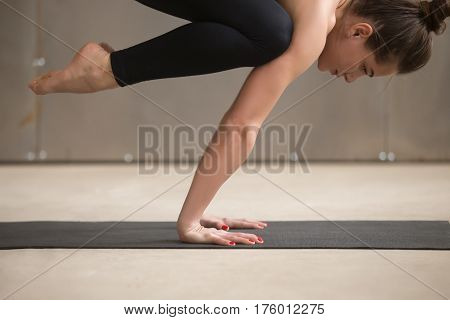 Young attractive yogi woman practicing yoga, standing in Bakasana exercise, Crane pose, working out, wearing black sportswear, cool urban style, grey studio background, close up, side view