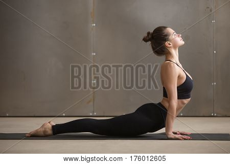 Young attractive yogi woman practicing yoga, stretching in Urdhva mukha shvanasana exercise, upward facing dog pose, working out, wearing black sportswear, cool urban style, full length, grey studio