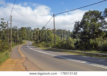Uphill rural asphalt road and green trees leading up hillside against blue cloudy sky in South Africa