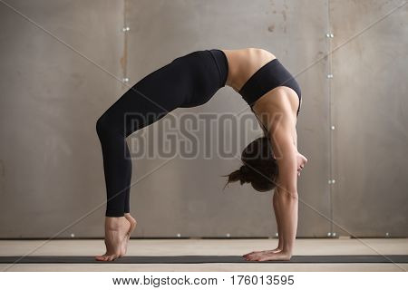 Young attractive yogi woman practicing yoga, standing in Urdhva Dhanurasana exercise, Bridge pose, working out wearing black sportswear, cool urban style grey studio background, full length side view