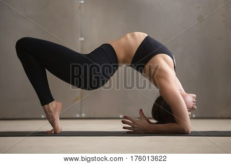 Young attractive yogi woman practicing yoga, stretching in Elbow Bridge exercise, Urdhva Dhanurasana pose, working out, wearing black sportswear, cool urban style, full length, grey studio background