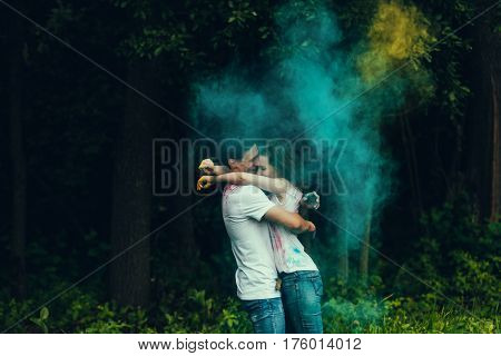 happy young couple kiss and hugs in paints holi