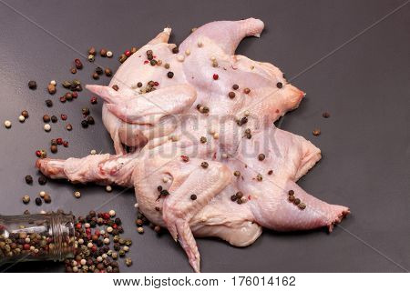 raw chicken carcass with peppercorns on a dark background.