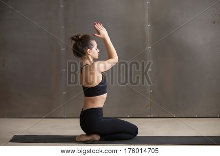 Young attractive yogi woman practicing yoga, sitting in vajrasana exercise, seiza pose, working out, wearing black sportswear, cool urban style, full length, grey studio background, side view