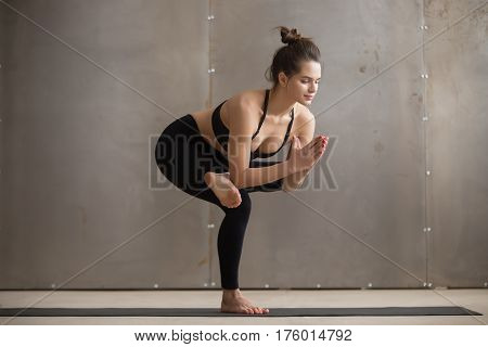 Young attractive yogi woman practicing yoga, standing in Utkatasana exercise, one legged Chair pose, working out, wearing black sportswear, cool urban style, full length, grey studio background