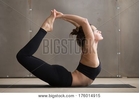 Young beautiful yogi woman practicing yoga, stretching in Dhanurasana exercise, Bow pose, working out, wearing black sportswear, cool urban style, full length, grey studio background, profile view