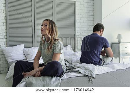 Upset husband and wife are sitting on different sides of bedstead. Woman looking up with indifference