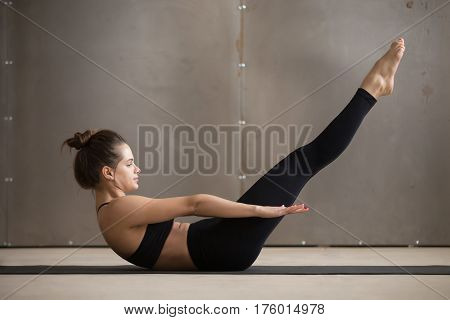 Young attractive sporty woman practicing yoga or fitness, doing boat exercise, working out, wearing black sportswear, cool urban style, full length, grey studio background, side view