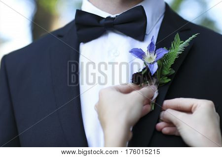 Closeup photo of bride adjusting boutonniere with clematis on grooms jacket