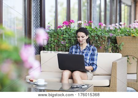 Beautiful young freelancer woman using laptop computer sitting at cafe table. Happy smiling girl working online or studying and learning while using notebook. Freelance work business people concept
