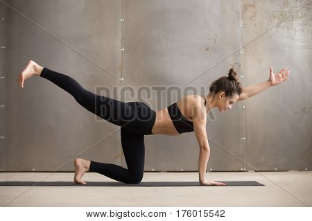 Young attractive woman practicing yoga, standing in Bird dog pose, Donkey Kick exercise, working out, wearing black sportswear, cool urban style, full length, grey studio background, side view