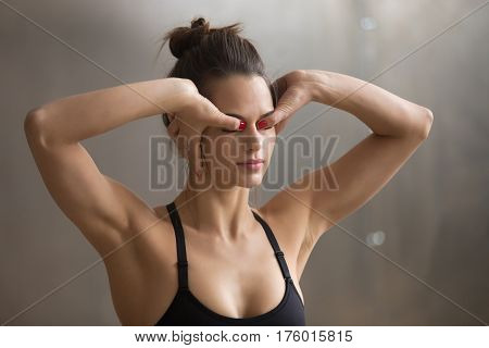 Portrait of young attractive yogi woman doing yoga, practicing Kriya technique for eyes and stress relief, working out, cool urban style, closeup, grey studio background