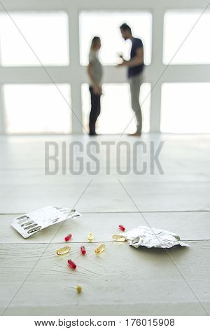 Suicide problem. Different kinds of tablets are lying on parquet. Married couple is arguing on background