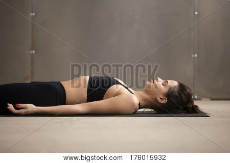 Young attractive woman practicing yoga, lying in Dead Body, Savasana exercise, Corpse pose, working out, wearing black sportswear, cool urban style, closeup, grey studio background