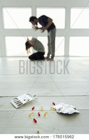 Focus on different kinds of capsules at floor. Angry man hitting woman