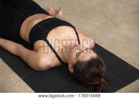 Young beautiful woman practicing yoga, lying in Dead Body, Savasana exercise, Corpse pose, working out, wearing black sportswear, cool urban style, closeup, grey studio background