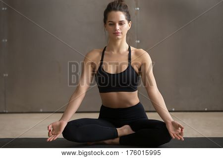 Young attractive happy yogi woman practicing yoga, sitting in Sukhasana exercise, Easy Seat pose with mudra, working out wearing black sportswear, cool urban style, full length, grey studio background