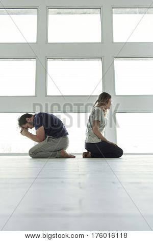 Conflict in family. Upset man is standing at knees. Sad woman turning back to him