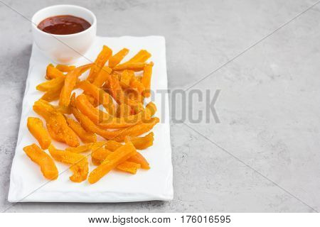 Healthy baked sweet potato fries on white plate served with spicy sauce copy space