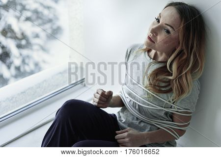 Frustrated female person is bound with rope. She sitting near wall and looking aside. Portrait