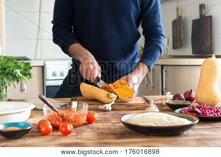 Man prepares a dish of squash stuffed with rice and cranberries on a wooden table in the kitchen. Tasty and healthy food
