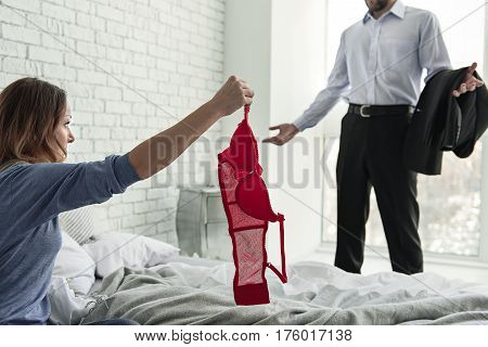 Upset woman is keeping scarlet bra and demonstrating it to her husband. He making helpless gesture
