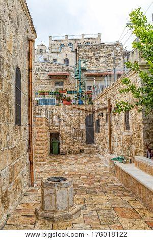 JERUSALEM, ISRAEL - MAY 24, 2016: Greek orthodox church of Saint John the Baptist exterior, yard and old well.
