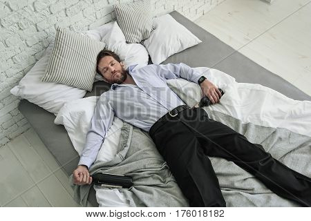 Man is holding bottles with alcohol. He sleeping at bedstead. Top view