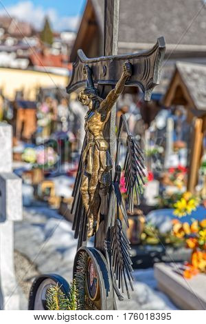 SAPPADA, ITALY - FEBRUARY 20, 2017: Wrought crucifix on tombstone on the catholic cemetery on a winter day.