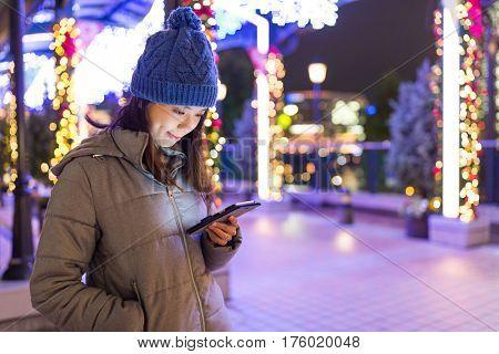 Woman sending sms on cellphone in Yokohama night