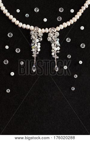 Handmade gentle wedding bijouterie : earrings with crystals and white pearl necklace lying flat on the vertical black background top view