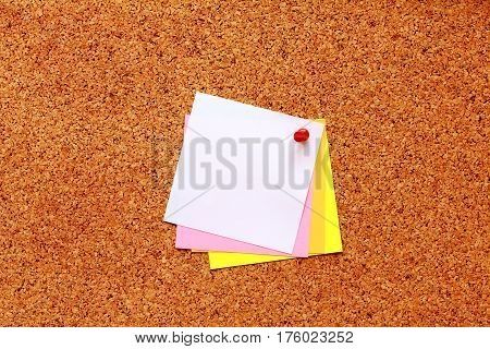 White sticky notes with pin on a cork board
