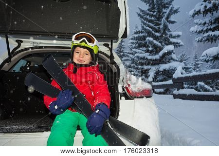 Happy boy in safety helmet and mask sitting in car trunk after ski trip in evening