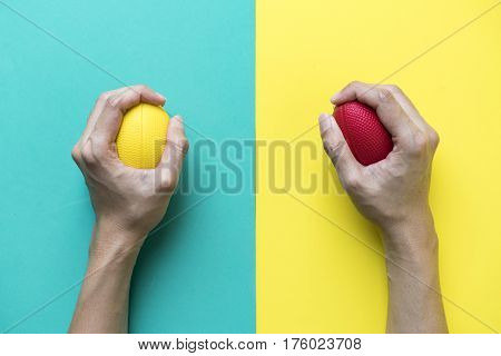 Hands of a woman holding a stress ball on colorful background