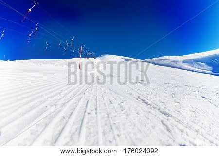 Tracks of snowcat on the packed snow next to the ropeway at ski resort