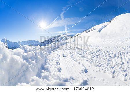Beautiful mountain scene with snowy alpine path for skiing