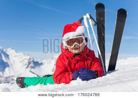 Cute little skier in Santa's hat laying on the snow with skis and poles forcing into the bank